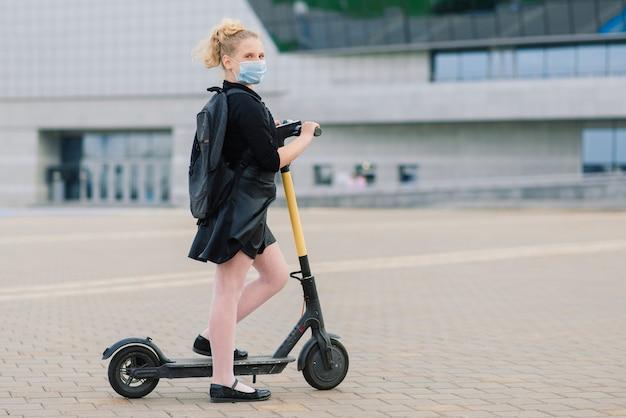 Meisje met een masker verlaat haar huis om op een scooter naar school te gaan