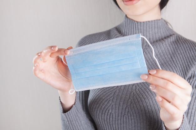 Meisje met een medisch masker in haar hand
