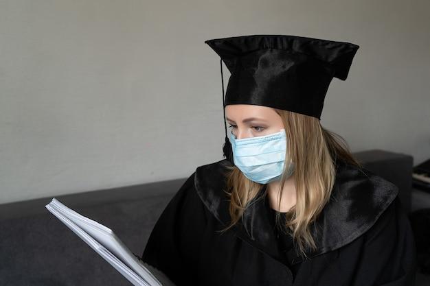 Meisje met een medisch masker met een hoed met een afstudeerjurk die een notitieboekje vasthoudt en ernaar kijkt op een grijze achtergrond