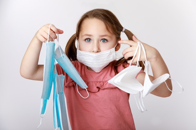 Meisje met een medisch masker op haar gezicht dat veel medische en ffp2-maskers vasthoudt Premium Foto