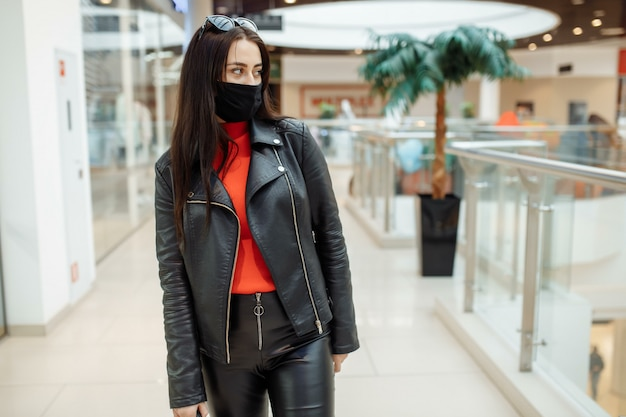 Meisje met een medisch zwart masker loopt langs een winkelcentrum. coronapandemie. meisje in een beschermend masker is winkelen in het winkelcentrum