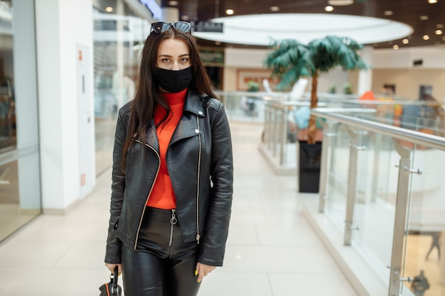 Meisje met een medisch zwart masker loopt langs een winkelcentrum. coronapandemie.