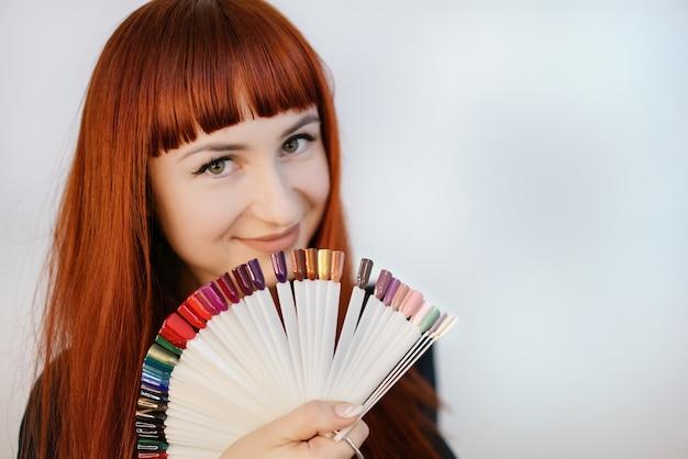 Meisje met een mooie manicure, die in haar handen steekproeven van manicure houdt. portret van een vrouw met rood haar.