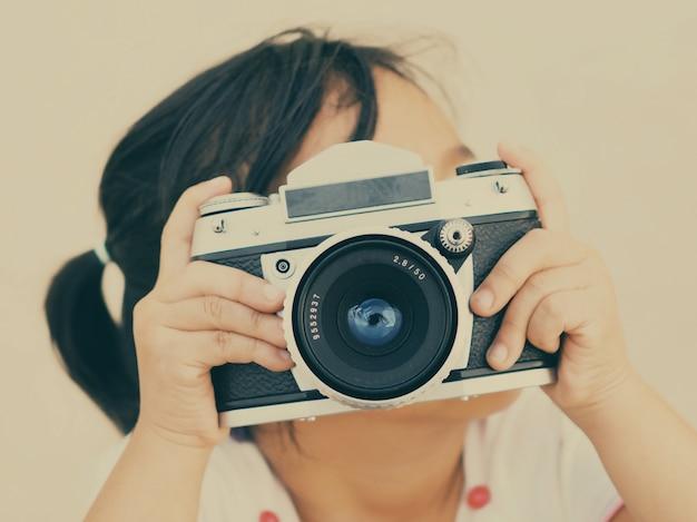 Meisje met een oude fotocamera