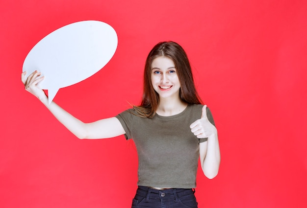 Meisje met een ovale informatiebord met duim omhoog teken.