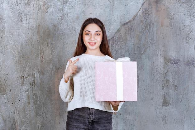 Meisje met een paarse geschenkdoos omwikkeld met een wit lint.