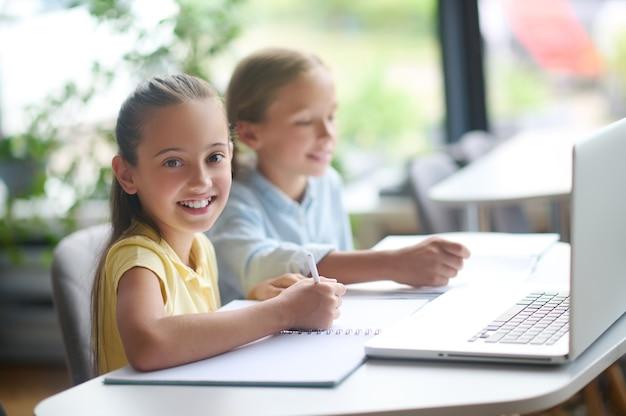 Meisje met een pen en haar klasgenoot aan het bureau