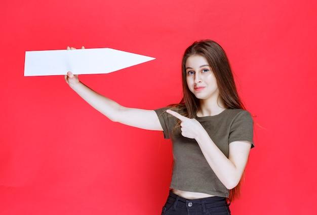 Meisje met een pijl die naar rechts wijst.