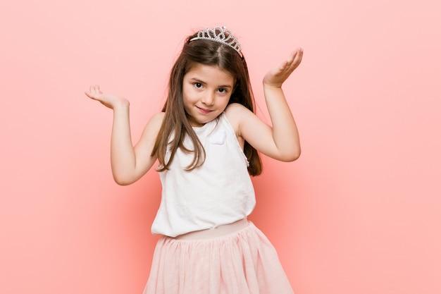 Meisje met een prinseslook maakt schaal met armen, voelt zich gelukkig en zelfverzekerd