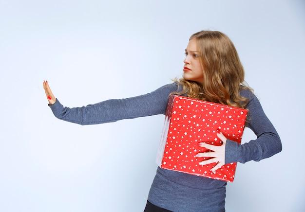 Meisje met een rode geschenkdoos die mensen tegenhoudt.