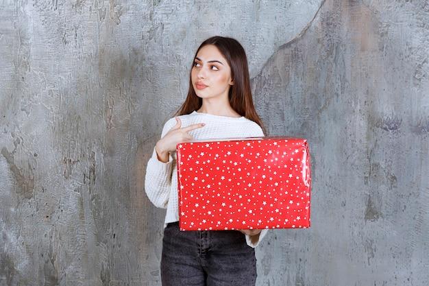 Meisje met een rode geschenkdoos met witte stippen erop en ziet er attent en dromerig uit.