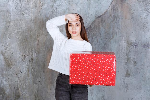 Meisje met een rode geschenkdoos met witte stippen erop en ziet er moe uit.