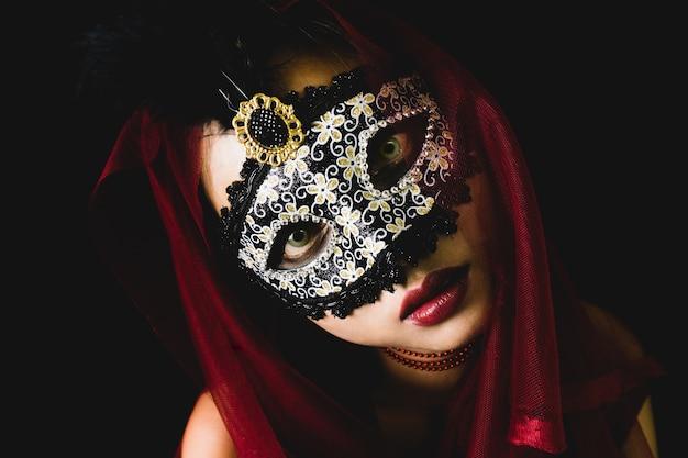 Meisje met een rode sjaal op haar hoofd en een venetiaans masker