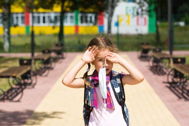 Meisje met een rugzak bij de school nadat de lessen een medisch masker hebben afgezet, ongelukkig
