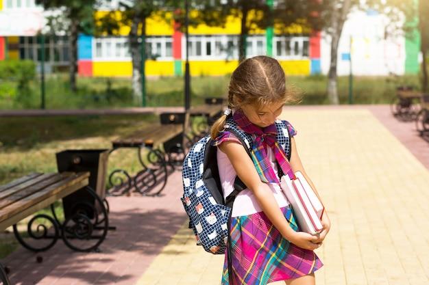 Meisje met een rugzak en een stapel boeken in de buurt van de school. terug naar school, het kind is moe, zware leerboeken. onderwijs, basisschoolklassen, het begin van het schooljaar, 1 september