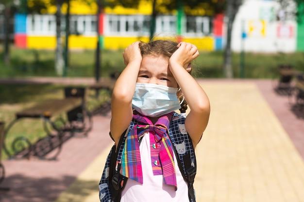 Meisje met een rugzak in de buurt van de school nadat de lessen een medisch masker afzetten, ongelukkig, moe en hoofdpijn. hij houdt zijn hoofd met zijn handen vast, er is zuurstoftekort. coronavirus, veiligheidsmaatregelen