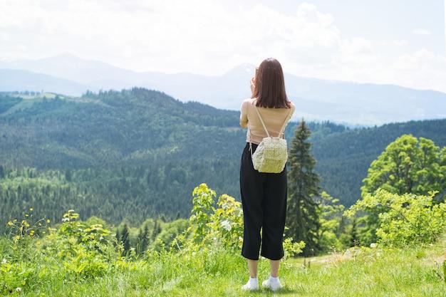 Meisje met een rugzak op een smartphone foto's van bergen en bossen.