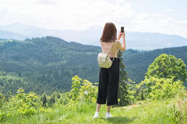 Meisje met een rugzak op een smartphonefoto's van bergen en bos. achteraanzicht. zonnige zomerdag