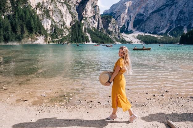 Meisje met een schipper in haar handen en camera kijken. jonge vrouw die zich voordeed op de oever van het schilderachtige bergmeer. dolomieten, italië, europa.