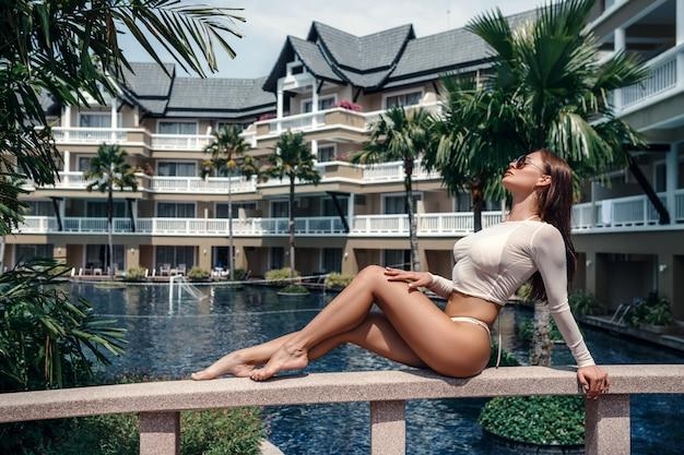 Meisje met een slank figuur ligt op de reling van de brug van het hotel