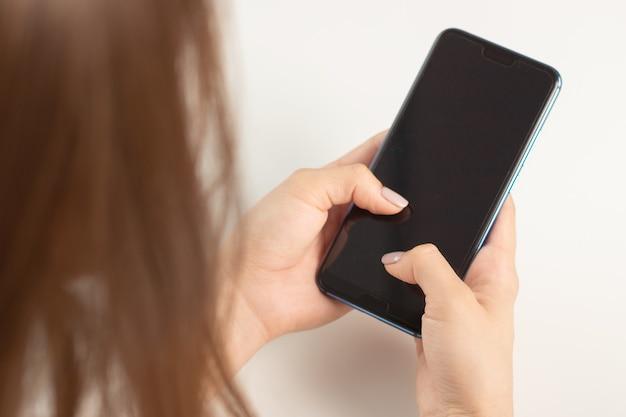 Meisje met een smartphone die tekst op het scherm typt