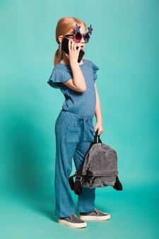 Meisje met een staart in stijlvolle kleding en zonnebril op blauw