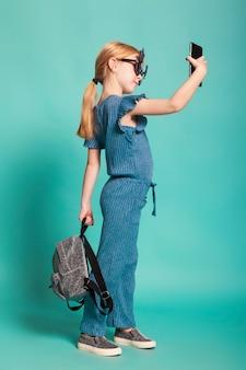 Meisje met een staart in stijlvolle kleding en zonnebril