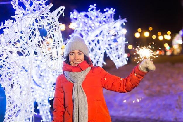 Meisje met een sterretje in haar hand. buiten winter stad achtergrond, sneeuw, sneeuwvlokken.