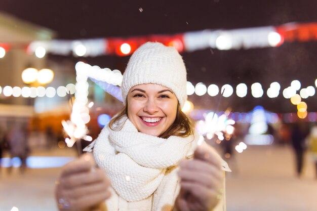 Meisje met een sterretje in haar hand buiten winter stad achtergrond sneeuw sneeuwvlokken