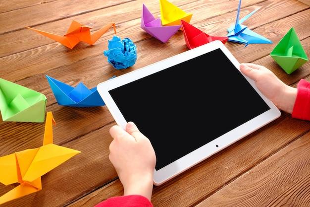 Meisje met een tablet in zijn handen aan tafel