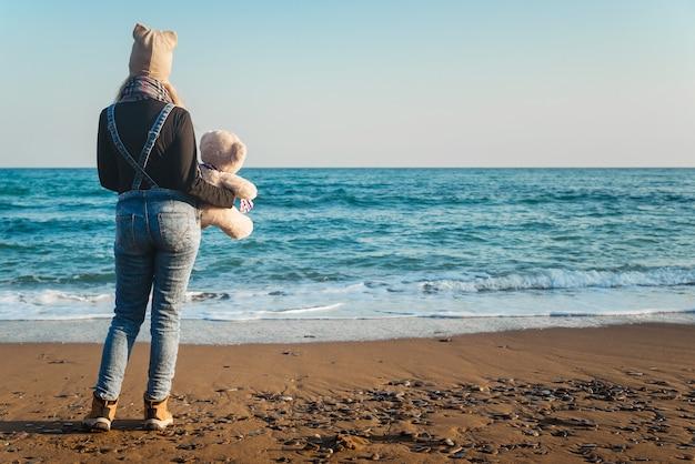 Meisje met een teddybeer in handen aan de kust op een heldere dag, uitzicht op de achterkant