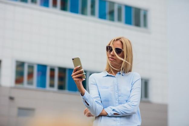 Meisje met een telefoon op bedrijfs de bouwachtergrond. mooi blond meisje met een bril