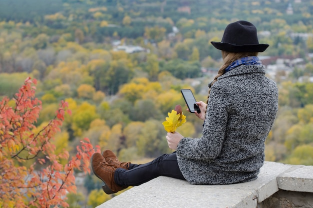 Meisje met een telefoon zit op een heuvel, gele bladeren in haar hand