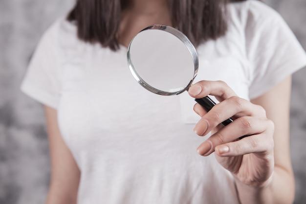 Meisje met een vergrootglas in zijn handen zoeken naar informatie