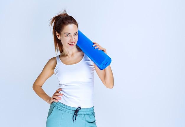 Meisje met een vervaging opgerolde yoga mat.