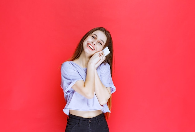 Meisje met een visitekaartje en glimlachen.