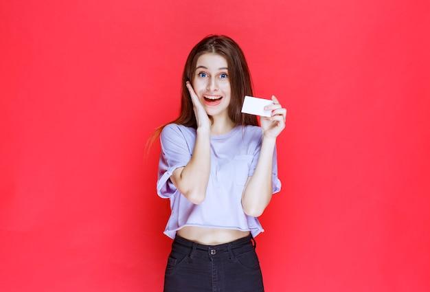 Meisje met een visitekaartje en kijkt verrast en opgewonden.