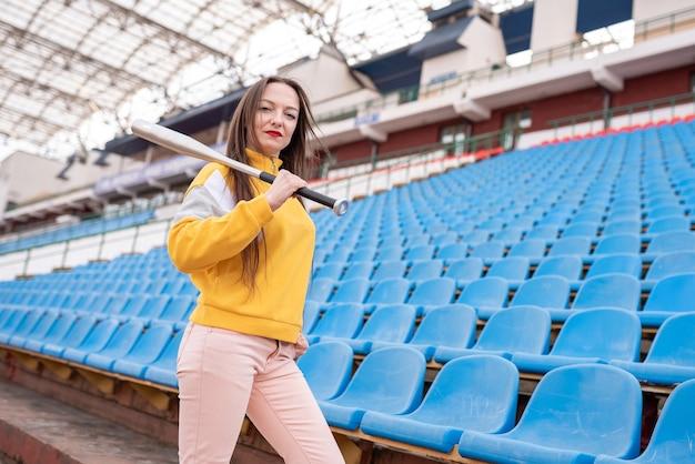 Meisje met een vleermuis in een leeg stadion. voor elk doel
