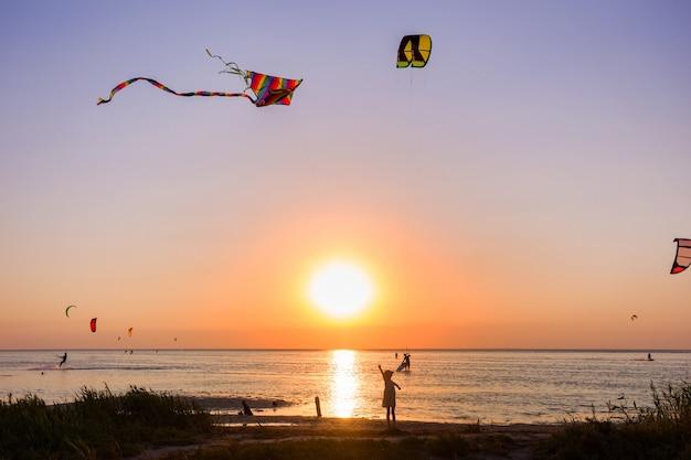 Meisje met een vlieger op zee in zonsondergangtijd