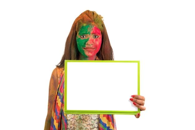 Meisje met een wit bord met gezicht beschilderd met kleur in festival of color holi. geïsoleerde portret