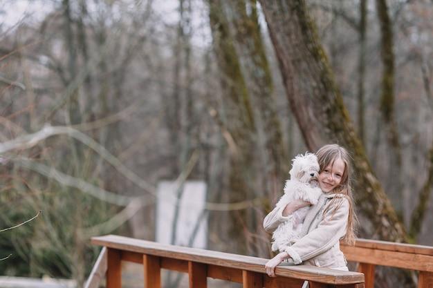 Meisje met een wit puppy. een puppy in de handen van een meisje