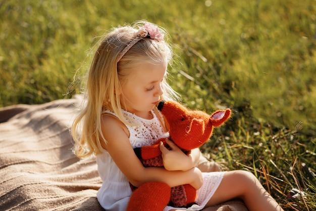 Meisje met een zacht stuk speelgoed in de natuur