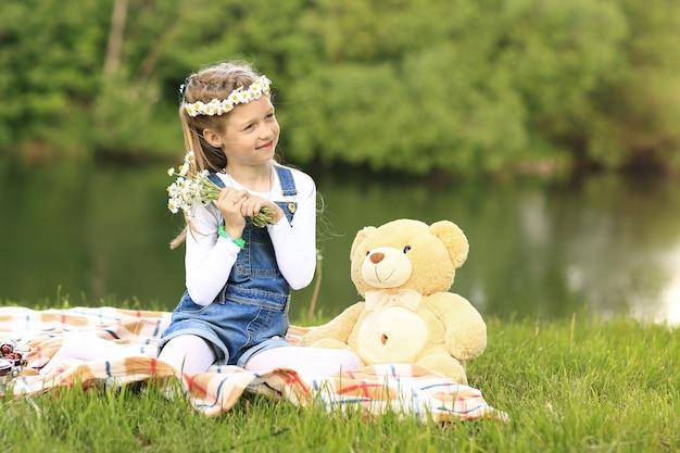 Meisje met een zacht stuk speelgoed op een picknick in de buurt van de rivier op een zonnige dag
