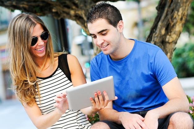 Meisje met een zonnebril met iets op de tablet aan haar vriend
