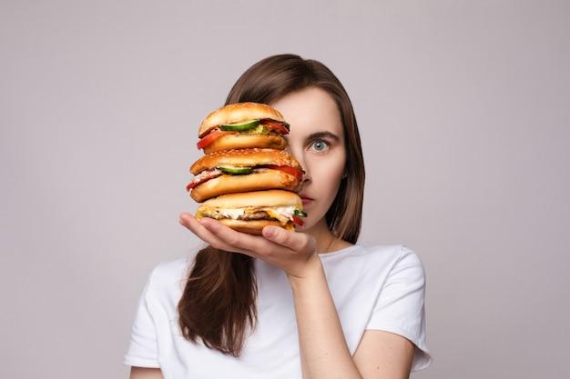 Meisje met enorme hamburger bij de hand. studio portret van jonge brunette vrouw in wit t-shirt met enorme hamburgers aan haar hand op zoek geschokt of verrast