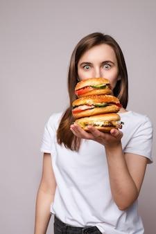 Meisje met enorme hamburger bij de hand. studio portret van jonge brunette vrouw in wit t-shirt met enorme hamburgers op haar hand op zoek geschokt of verrast op camera.