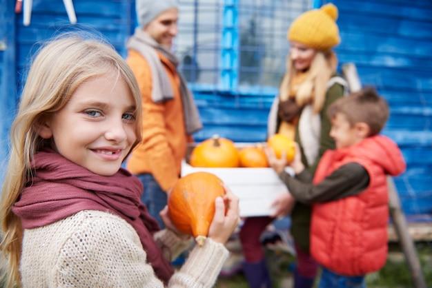 Meisje met familie tijdens de herfstoogst