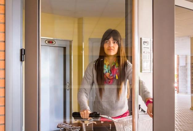 Meisje met fixiefiets die een glazen deur opent om af te sluiten