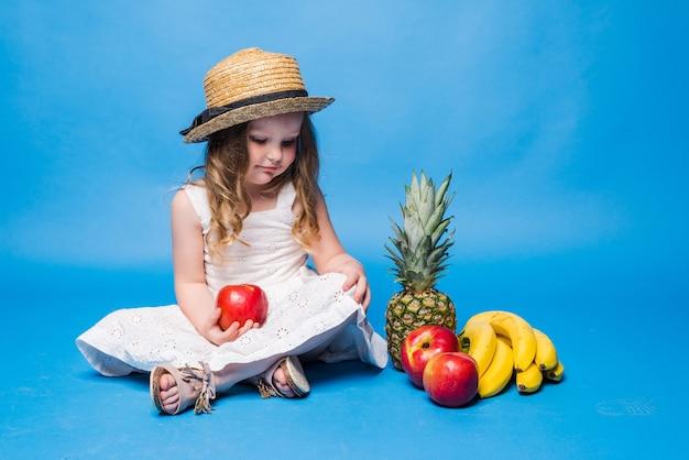 Meisje met fruit dat op blauwe muur wordt geïsoleerd