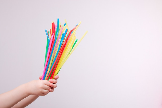 Meisje met gebruikte wegwerp plastic rietjes